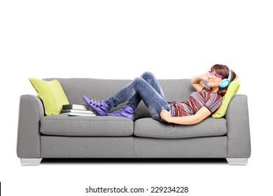 Young woman listening music on headphones and lying on a sofa isolated on white background