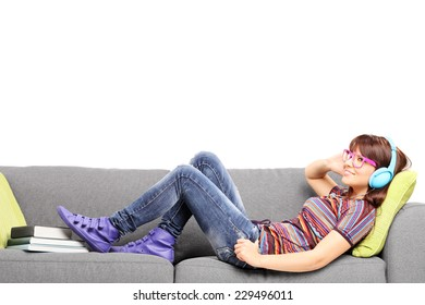 Young woman listening music on headphones and lying on a couch isolated on white background