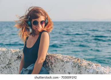 Young woman listening to the music on headphones by the sea
