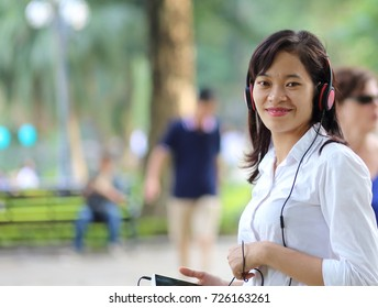 Young woman listening to music on a smartphone in Hanoi