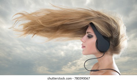 Young woman  listening to music on headphones wind nazvivaet hair