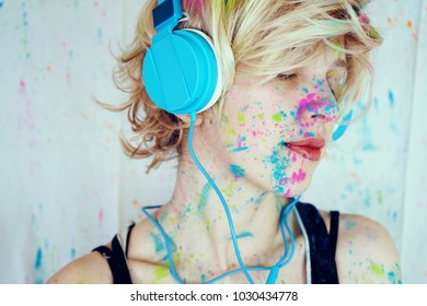 Young woman listening to music with paint in her face