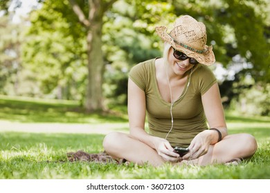 Young woman listening to music in a park