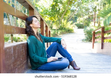 Young woman listening to music at the park
