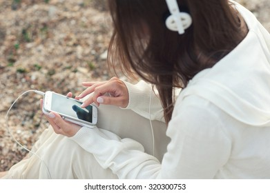 Young woman listening music with phone against sea sand backdrop, back view.