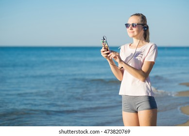 Young woman is listening a music from smartphone on the beach