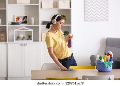 Young woman listening to music while cleaning her flat