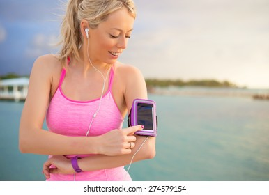 Young woman listening to music while working out outdoors in early morning