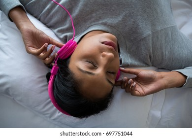 Young woman listening to music while sleeping on bed at home