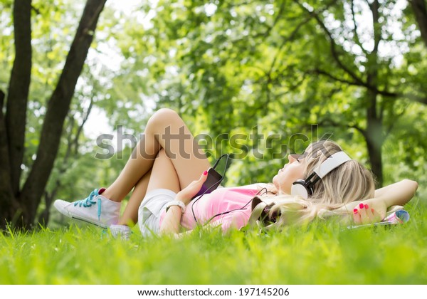 Young woman listening to music while lying down on grass