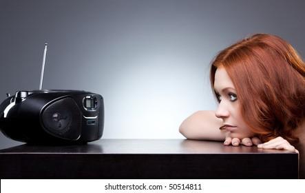 Young woman listening radio. Boring mood.