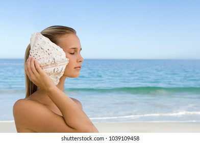 Young woman listening to shell