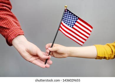 Young woman and little child holding american flag. Independence Day concept. Family together