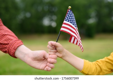Young woman and little child holding american flag on grey background. Independence Day concept. National holiday. Family together