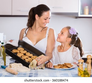 Young woman and little european  girl holding baking tray with scones