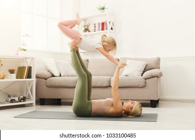 Young woman and little girl doing partner yoga flying pose, exercising together at home. Mother and daughter activity, acroyoga. Trust and support concept