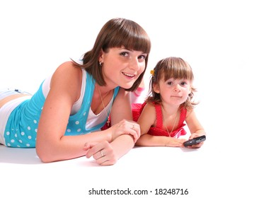 A young woman and a little girl with a mobile phone lying together ovr white background