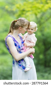Young woman and little girl in the park. Mother kisses her charming daughter on open air