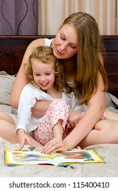 Young woman and little girl read a book sitting on bed