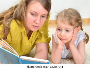 Young woman and little girl read a book
