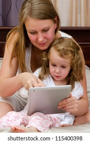 Young woman and little girl using tablet pc sitting on bed