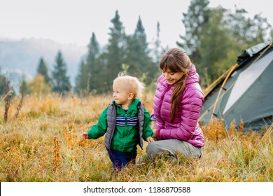 Young woman, little toddler kid having fun over camping tent at scenic forest view. Hiking activity, travel adventure with child. Exploring nature on family autumn fall vacation, weekend walking tour.
