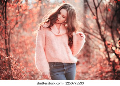 Young woman in Living Coral forest. Color of the year 2019. Main trend natural and authentic concept.