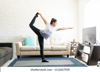 Young woman in living room practicing lord of the dance yoga pose