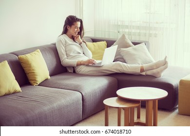 Young woman in living room surfing the internet