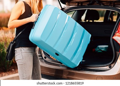 Young woman loading two blue plastic suitcases to car trunk. Preparation for trip