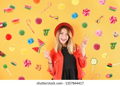 Young woman with lollypops and flying candies on color background