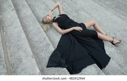 young woman in a long black dress lying on the stairs
