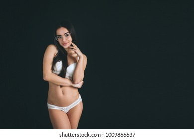 Young woman with long black hair wearing glasses stands isolated on black background. The girl has a sports figure, she is dressed in white underwear. Beautiful panties and bra
