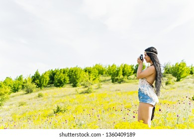 Young woman with long black hair in boho outfit outdoors taking a photo on vintage camera. Natural lighting, no retouch. copy space available.