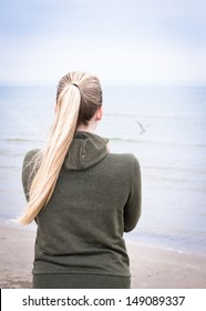 Young woman with long blond ponytail on a foggy morning looking at the sea. There is a gull above the water, but you can see only light shade of it.