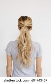 A young woman with long blond wavy hair tied in a ponytail Back view