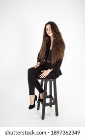 Young woman with long brown hair in black clothes and high heels sitting on a bar stool. White background. Vertical view