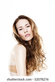 young woman with long brown hair wearing a bra isolated against a white background.