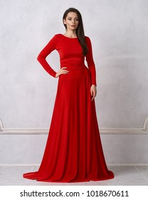 Young woman with long brunette hair dressed in elegant evening red maxi dress with long sleeves posing in studio. Gorgeous female model standing against white wall decorated with classic moldings.