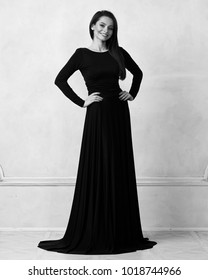 Young woman with long brunette hair dressed in elegant evening black maxi dress with long sleeves posing in studio. Gorgeous female model standing against white wall decorated with classic moldings.