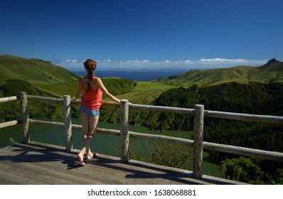 Young woman with long dark hair in red shirt and denim jeans standing near barrier on a precipice. View from behind. Viewing point. Bright green ladscape and blue sky with clouds, incredible view of