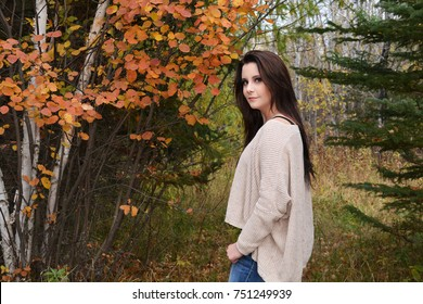 Young woman with long dark hair standing in the woods by a birch tree with orange leaves