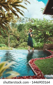 A young woman in a long dress of emerald color and wearing a hat walks over the side of an open private pool overlooking the tropical jungle, Ubud,Bali.Private pool with rose petals in a luxury hotel