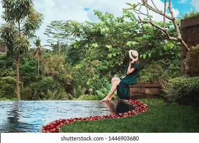 A young woman in a long dress of emerald color and wearing a hat sits by the open personal pool overlooking the tropical jungle, Ubud, Bali. Private pool with rose petals in a luxury hotel in Bali