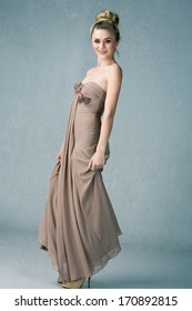 Young woman in long dress and hair in top knot bun on grey grunge studio background