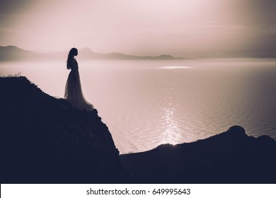 Young woman in long dress standing on a rock and looking to a sea