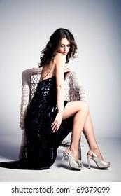 young woman in long elegant dress, sit in arm chair, full body shot, studio shot