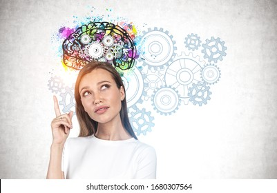 Young woman with long fair hair pointing upwards standing near concrete wall with colorful brain sketch and gears drawn on it. Concept of brainstorming and creativity