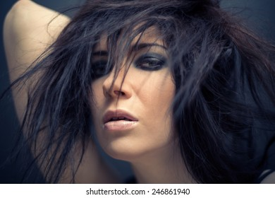 Young woman with long hair against a dark background. shallow depth of field
