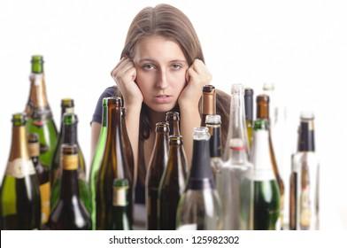 Eine junge Frau mit langer Haarbrunette sitzt inmitten leerer Flaschen auf einem Tisch und sieht verzweifelt aus, einzeln auf weißem Hintergrund.
